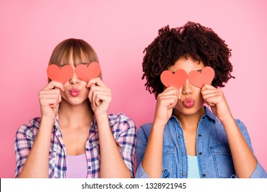 Close-up portrait of two person nice lovely sweet attractive cheerful girls in checkered shirt closing covering eyes with small little cards send you kiss isolated over pink pastel background