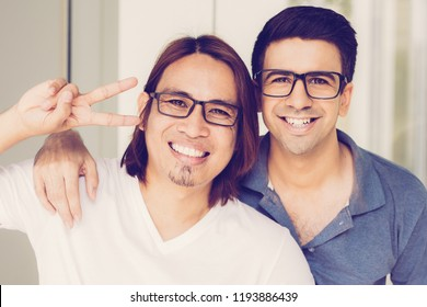 Closeup portrait of two smiling handsome young men looking at camera, showing victory sign and posing outdoors with building in background. Men friendship concept. Front view.