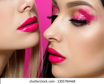 Closeup portrait of two young beautiful women with fashion pink makeup. Bright pink lip gloss and eye shadows. Skin care, cosmetics, SPA therapy or cosmetology concept