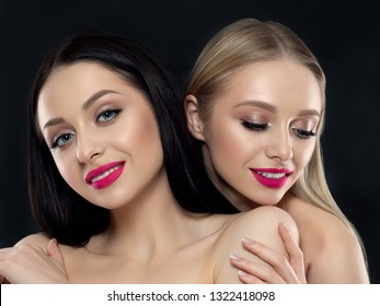 Closeup portrait of two young beautiful smiling women over black background. Bright pink lipstick. Skin care, cosmetics, SPA therapy or cosmetology concept