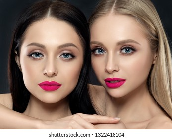 Closeup portrait of two young beautiful women over black background. Bright pink lipstick. Skin care, cosmetics, SPA therapy or cosmetology concept