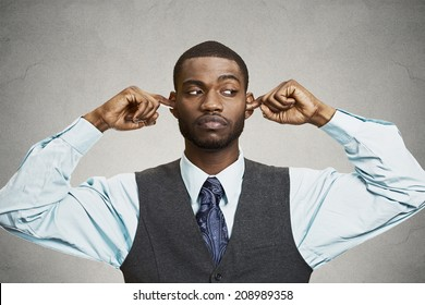 Closeup portrait unhappy, annoyed man plugging closing ears with fingers, disgusted ignoring something not wanting to hear someone side story, isolated grey background. Human emotion body language