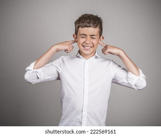 Closeup portrait unhappy, annoyed young man plugging closing ears with fingers disgusted ignoring something not wanting to hear someone side story isolated grey background. Human emotion body language