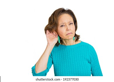 Closeup portrait, unhappy hard of hearing senior mature woman placing hand on ear asking someone to speak up bad news, isolated white background. Negative emotion, facial expression, feeling, reaction