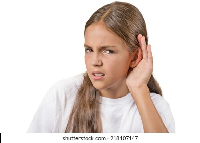 Closeup portrait unhappy hard of hearing young girl placing hand on ear asking someone speak up, listening bad news isolated white background. Negative emotion facial expression feeling body language