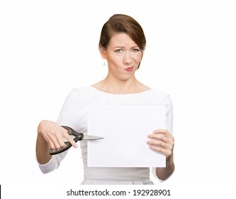 Closeup portrait, unhappy, skeptical, confused, displeased business woman, funny female, worker, employee cutting blank white paper, copy space, scissors isolated white background. Facial expressions