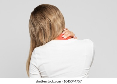 Closeup portrait of unhealthy blonde female in white top with pain in her neck and back, coloured in red, back view/ Cervical arthritis, osteochondrosis, diseases of the musculoskeletal system concept