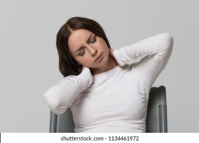Closeup portrait of unhealthy cute female in white top with pain in her neck and back. Cervical arthritis, osteochondrosis, diseases of the musculoskeletal system concept.Fatigue, headache, overwork