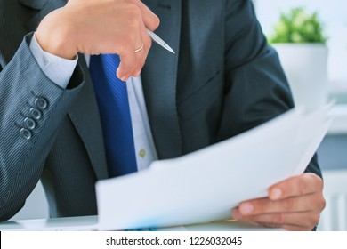 Closeup portrait of unrecognizable businessman in black formal suit reading contract documents at the desk in the office.