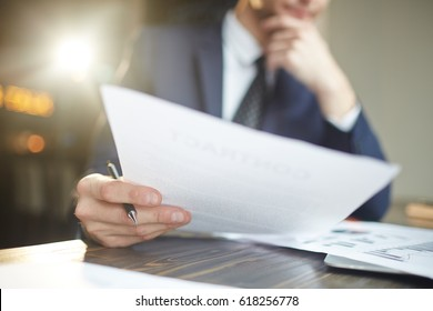 Closeup portrait of unrecognizable successful businessman wearing black formal suit analyzing documents and finance statistics at desk, thinking