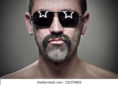 close-up portrait of unshaven man in sunglasses