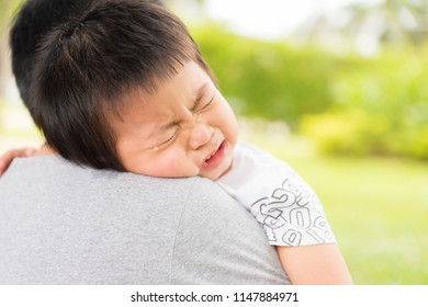 Closeup portrait of upset little girl crying on her mothers shoulder in garden background, happy young loving family, new life concept.