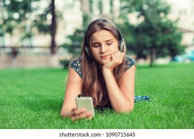 Closeup portrait upset sad skeptical unhappy serious woman texting on phone displeased bored worried with conversation lying down in city park background Negative human emotion face expression feeling