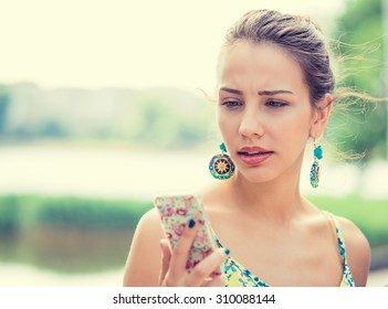 Closeup portrait upset sad skeptical unhappy serious woman talking texting on phone displeased with conversation isolated park outdoors background. Negative human emotion face expression feeling