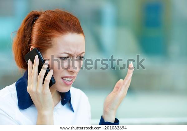 Closeup portrait upset sad, skeptical, unhappy, serious woman talking on phone, walking in hallway isolated office background. Negative human emotion facial expression feeling, life reaction. Bad news