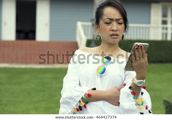 Closeup portrait upset sad skeptical unhappy serious woman talking texting on phone displeased with conversation isolated outdoors park background. Negative human emotion face expression feeling