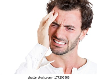 Closeup portrait of upset, stressed out young sick, tired man, handsome sad student having headache, bad day at work, school, isolated on white background. Negative human emotions, facial expressions