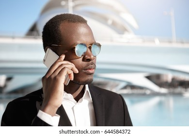 Close-up portrait of urban entrepreneur with dark skin wearing round glasses and formal clothes holding his smart phone talking with his partner having serious look. Business and career concept