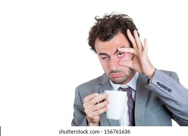 A close-up portrait of a very tired, falling asleep businessman holding a cup of coffee, struggling not to crash and stay awake, keeping his eyes opened, isolated on a white background with copy space