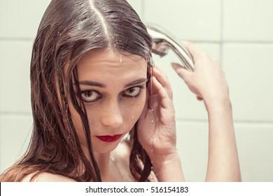 Close-up portrait of a wet sad woman under washer