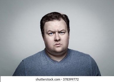 Close-up portrait of white Caucasian big fat stout man with blue eyes looking directly in camera in studio on light background, skeptical suspicious expression, emotion