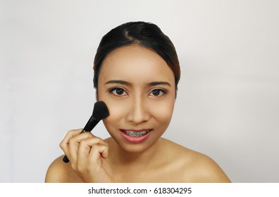 Close-up portrait. woman applying blush on. She is smiling.