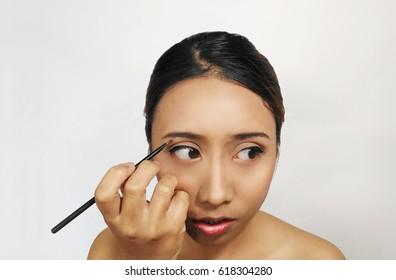 Close-up portrait. woman applying eyeshadow on her eyebrow.