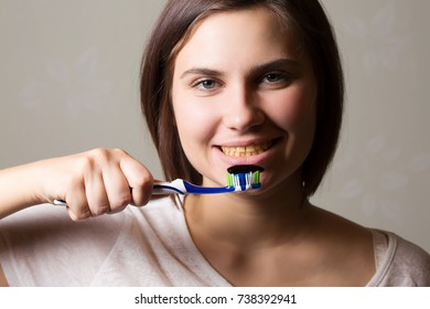 close-up portrait woman cleaning yellow teeth. black toothpaste