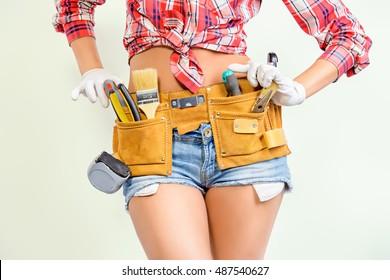 Close-up portrait of a woman construction worker wearing tool belt. Building, repair concept.