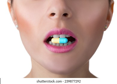 close-up portrait of woman face with perfect skin and mouth with coloured pill between teeth