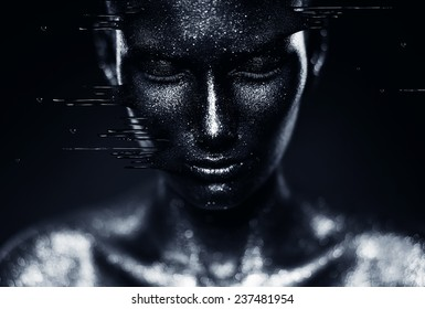 close-up portrait of woman in flowing black paint in dark