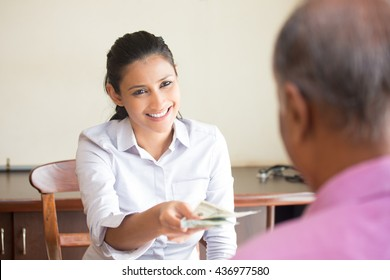 Closeup portrait, woman giving cash back refund, isolated indoors office background.  Excellent customer service with a smile
