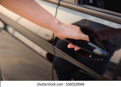 Close-up portrait of woman hand holding handle to open a cars door.