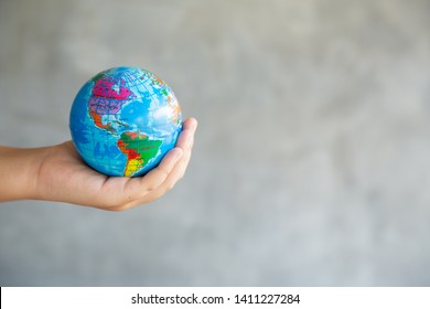 Close-up Portrait of Woman is Holding Global in Her Hands on gray Background. Save The Planet and Traveling Conceptual. Save The Earth and Care Environment Concept.
