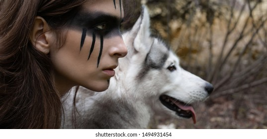 Close-up portrait of a woman hunter with war paint on her cheeks against the backdrop of a wolf face