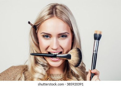 Closeup portrait of woman with makeup brush near face - Shutterstock ID 385920391