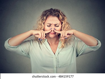 Closeup portrait woman pinches nose with fingers looks with disgust something stinks bad smell isolated on gray wall background. Human face expression body language reaction
