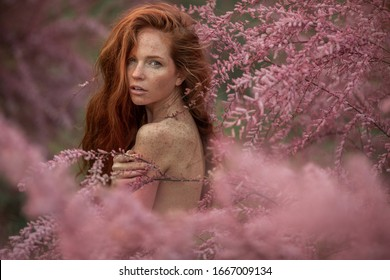 Close-up portrait of a woman in the pink branches of a flowering peach tree