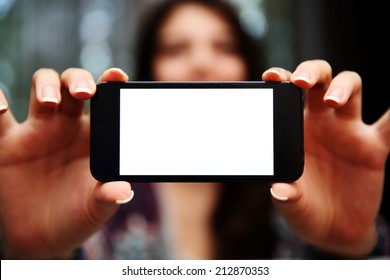Closeup portrait of a woman showing smartphone screen