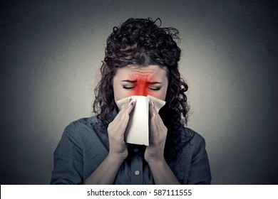 Closeup portrait woman sneezing in a tissue blowing her runny nose