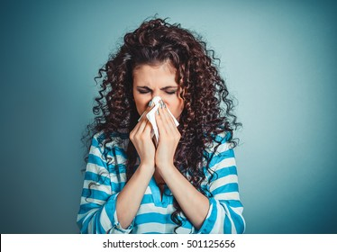 Closeup portrait of woman sneezing or using towel to wipe snot from her nose, isolated on blue background with copy space