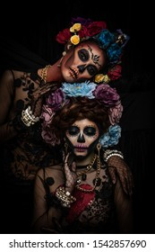 Closeup portrait of a woman with a sugar skull makeup dressed with flower crown. Halloween concept