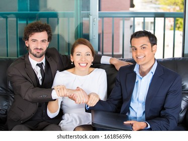 Closeup portrait of woman trying to force a deal and handshake between two men of different races sitting on black couch in apartment, home or office, isolated on a city urban background