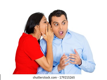 Closeup portrait of woman whispering into man's ear telling him some shocking office gossip. Surprised disbelief wide open mouth response. Positive human emotions facial expression feelings