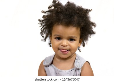 Close-up portrait of wonderful baby girl showing tongue at camera. Little beautiful well-dressed kid with curly hair posing inside. Isolated on white background