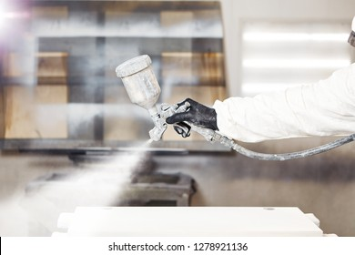 Close-up portrait of worker using spray gun and painting wood.