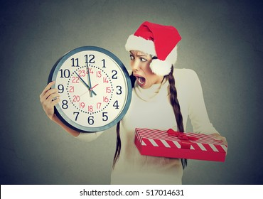 Closeup portrait worried stressed in a hurry young woman wearing red santa claus hat holding clock gift box isolated gray background. Emotion, funny face expression, last minute christmas shopping