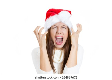 Closeup portrait of worried stressed overwhelmed young woman wearing red santa claus hat, screaming going crazy, isolated on white background. Emotion facial expression. Last minute christmas shopping