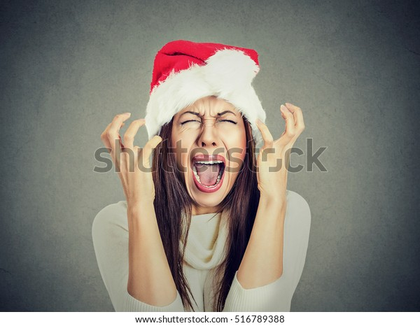 Closeup portrait of worried stressed overwhelmed young woman wearing red santa claus hat, screaming going crazy, isolated on gray background. Emotion facial expression. Last minute christmas shopping