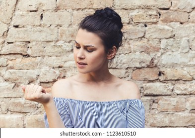 Closeup portrait worried woman looking at hand fingers nails obsessing about cleanliness isolated brick wall background. Negative human emotion facial expression feeling body language perception.